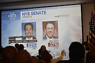 "Garden City, New York, USA. November 6, 2018. News 12 Long Island ""Island Vote 2018"" - projected on large screen - shows how candidates are doing in votes counted so far, as Nassau County Democrats watch Election Day results at Garden City Hotel, Long Island."