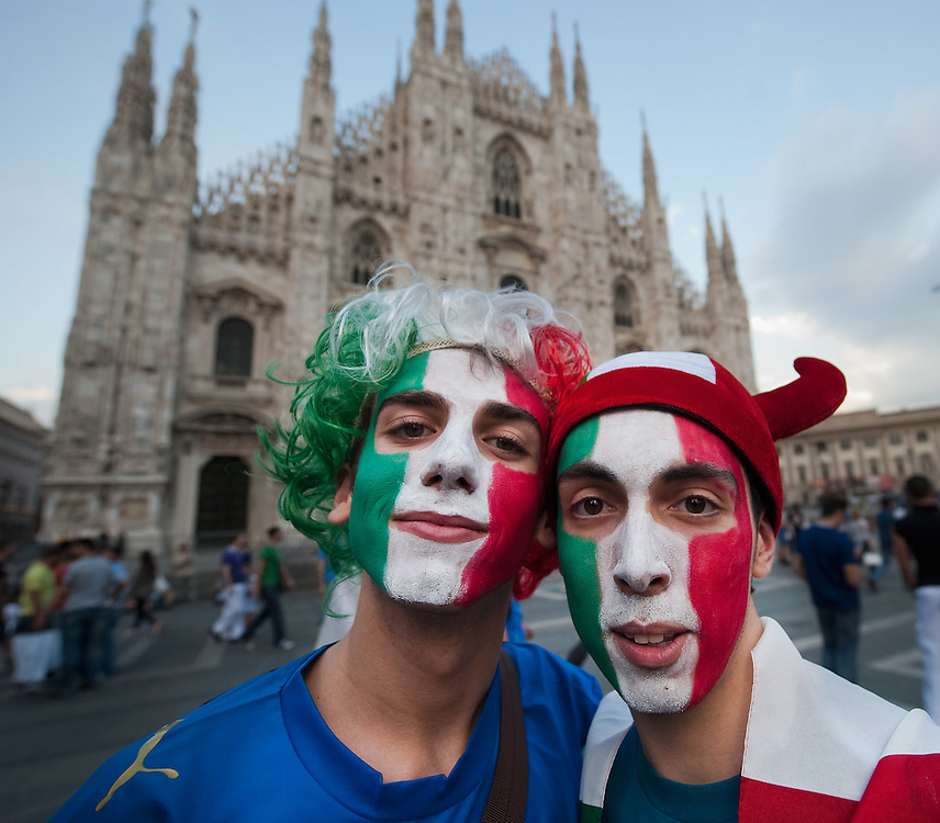 MILAN, ITALY - JUNE 14: Two Italian fans with faces painted in the colours of the Italian flag stand in Piazza del Duomo on June 14, 2010 in Milan, Italy. Italy's national football team managed a draw 1-1 against Paraguay in their first match of FIFA 2010Soccer World Cup.