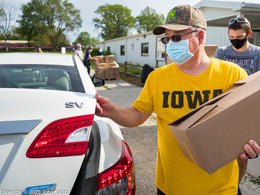 16 MAY 2020 - PERRY, IOWA:  A volunteer loads food into a car during a drive through Foodbank of Iowa emergency pantry at Crossroads Church in Perry. Food insecurity has skyrocketed in Iowa because of the pandemic shutdowns. The emergency pantry in Perry distributed all 200 meal boxes in less than 45 minutes. Emergency food pantry use has more than doubled in Perry since March. The Tyson pork processing plant in Perry is the community's largest employer. It had been shut down for deep cleaning because many workers in the plant tested positive for COVID-19. Since the start of the Coronavirus (SARS-CoV-2) pandemic and resulting shutdowns, nearly 300,000 Iowans, representing 20% of the eligible workforce, have applied for unemployment benefits in Iowa. Even though the Governor has reopened the Iowa economy, the number of COVID-19 infections continues to increase.       PHOTO BY JACK KURTZ