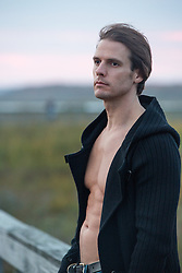 good looking man with an open sweater and no shirt outdoors in The Hamptons