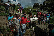 CÚA, VENEZUELA - AUGUST 17, 2017: Family and friends carry the coffin of three-month old, Kleiver Enrique Hernández through the cemetery to be buried. Kleiver was born healthy, weighing 8 pounds 2 ounces - however his mother Kelly Hernández had difficulty nursing him. Her nipples would bleed heavily while feeding him, causing Kleiver to reject being nursed. Infant formula was inaccessible as an alternative because of widespread shortages, so Kelly had to improvise with what was available.  She prepared bottles for Kleiver with cornstarch and water, or occasionally with whole milk, when she could find it. Milk is also very difficult to find in Venezuela because of shortages. He did not get the nutrients he needed to grow, and was not gaining enough weight. He went into septic shock due to severe malnutrition and died after 20 days in the hospital. PHOTO: Meridith Kohut for The New York Times