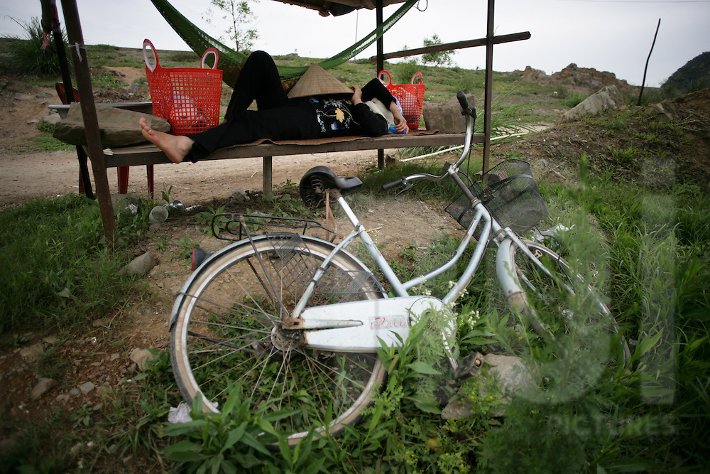 Woman resting on a bench with her bicycle lying beside in the countryside of Ninh Binh, Vietnam, Southeast Asia