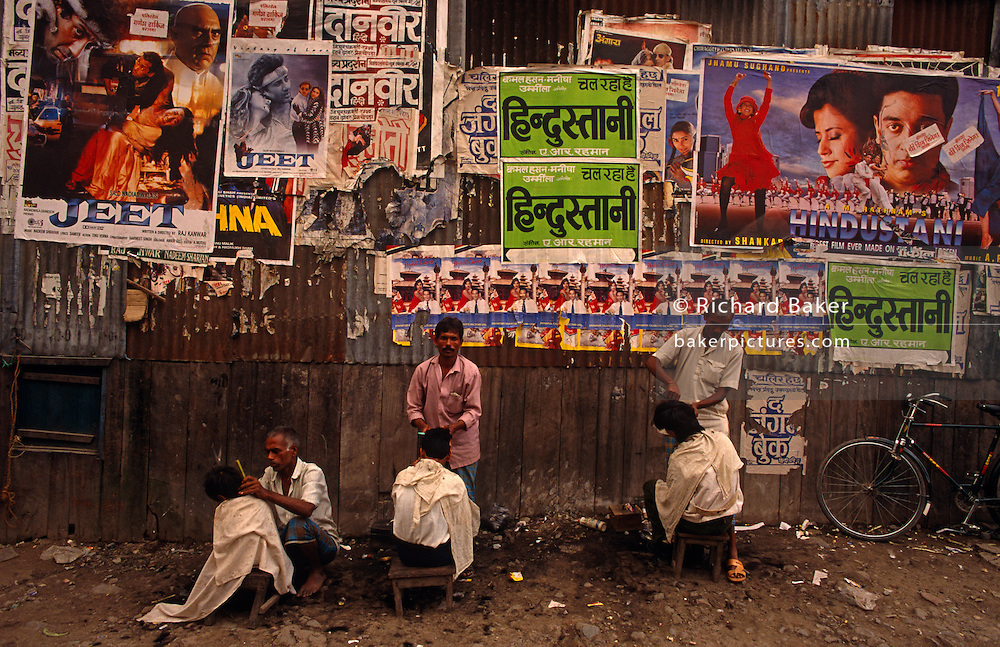Outdoor hairdressers cut customers' hair in a Calcutta street with heroic Bollywood movie posters on wall behind