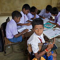 Pupils in class at the Thikilivattai Government Tamil Mixed School in Batticaloa District.<br /> <br /> Thikilivattai Government Tamil Mixed School reopened in May 2008 after local conflict between the LTTE and SLA  troops eased. There are now 351 students in grades 1-9 with a teaching staff of 18. The school has no water supply. Though many of the pupils' parents are not well educated themselves (most are employed in casual paddy cultivation, fishing and seasonal day-wage labour), there is a parents' mobilisation committee that encourages pupil attendance and is involved in helping keep the school clean. The school has an active sports department. Many of the students suffer with the trauma and stress associated with those living in conflict situations. The staff must deal with these issues as well as the personal difficulties that they themselves suffer living in a conflict environment. UNICEF have provided three temporary learning spaces to make up for the lack of space in the original school building. A further two classes must be accommodated beneath trees. UNICEF have also supplied the school furniture.<br /> <br /> Photo: Tom Pietrasik<br /> Batticaloa District, Sri Lanka<br /> September 30th 2009