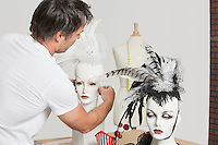 Back view of male fashion designer adjusting feather fascinator on mannequin