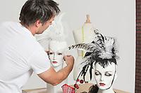 Back view of male fashion designer adjusting feather fascinator on mannequin