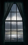 Winter storm clouds and crashing waves are illuminated by a brief patch of sunlight, seen through a window at Pigeon Point Light Station State Park, Pescadero, California