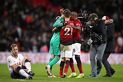 Tottenham Hotspur's Harry Kane reacts to an injury as Manchester United players celebrate after the final whistle