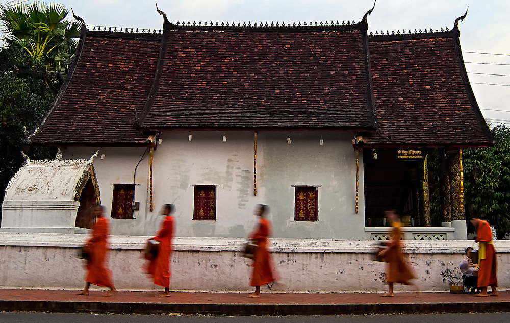 Buddhist monks walking the streets of Luang Prabang, Laos early in the morning collecting alms.