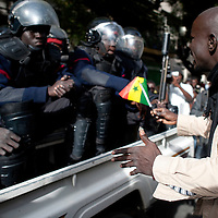 A man show Senegalese flag to riot police before clashes with protestors in the city center of Dakar on February 21, 2012. Senegal's opposition called for a new protest, prompting fears of fresh violence days before polls in which President Abdoulaye Wade's bid for a third term has upset the normally stable nation. ©Sylvain Cherkaoui