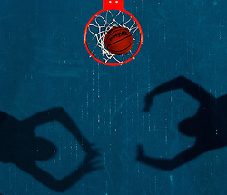 A Basketball in the hoop shadows of players loom on the court, EXPA Pictures © 2010, PhotoCredit: EXPA/ New Sport/ Matt A. Brown *** ATTENTION *** United States of America OUT!