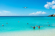 Two men wave at an approaching plane about to land at Princess Juliana International Airport in St. Maarten.