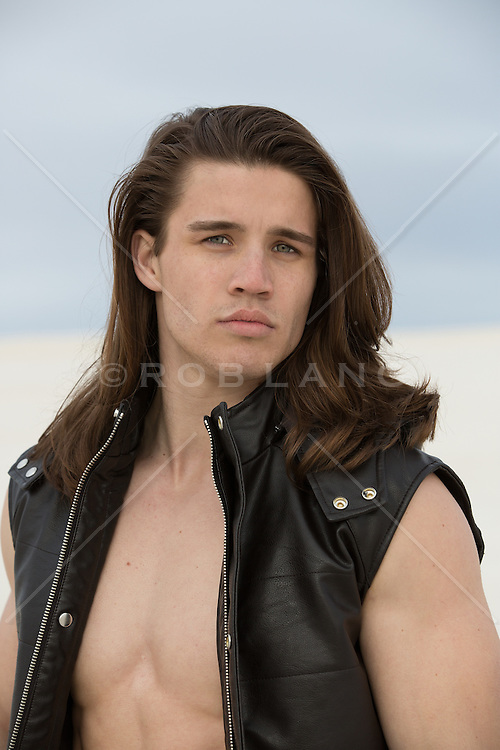 man with long brown hair in a leather vest and no shirt outdoors