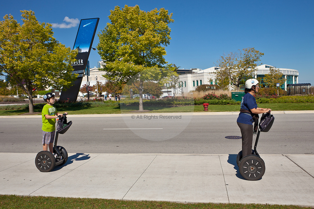 Segway riders pass the Adler Planetarium and Field Museum of Natural History in Chicago, IL, USA.