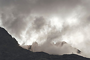Silhouette of a trail runner running  upnhill in Collado Jermoso on a foggy day, Leon, Spain Trail runner running uphill in Collado Jermoso, Picos de Europa National Park, Spain