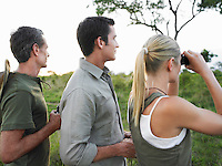 Two men and woman with binoculars side view