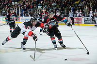 KELOWNA, CANADA, DECEMBER 3: Kevin Smith #3 of the Kelowna Rockets and Spencer Asuchak #16 of the Prince George Cougars fight for the puck as the Prince George Cougars visit the Kelowna Rockets  on December 3, 2011 at Prospera Place in Kelowna, British Columbia, Canada (Photo by Marissa Baecker/Shoot the Breeze) *** Local Caption ***