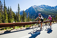 A young man and woman pedaling their bicycles up Washington Pass on Highway 20 in the North cascades of Washington State...Model releases: 20100716_MR_A.20100716_MR_B