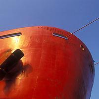 Proa con ancla de barco carguero rojo.