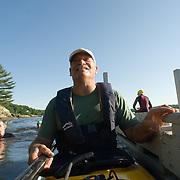 A smiling male kayak volunteer prepares his gear before the  2007 Shipbuilders Triathlon in Bath, Maine.