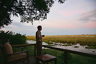 Man with cup of coffee looking at view from safari camp, Okavanga Delta, Botswana. http://www.gettyimages.com/detail/photo/morning-coffee-on-safari-botswana-royalty-free-image/119251840