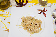 garlic olive oil and hot pepper spaghetti side view from above on white dish and on table cloth with spikes garnish, fork, hot pepper white wine and oextra virgin olive oilm, italian traditional food