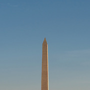 The top of the Washington Monument against a mostly clear blue sky in Washington DC.