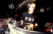 A DJ wearing headphones and FBI t-shirt examines a vinyl, U.K, 2000s.