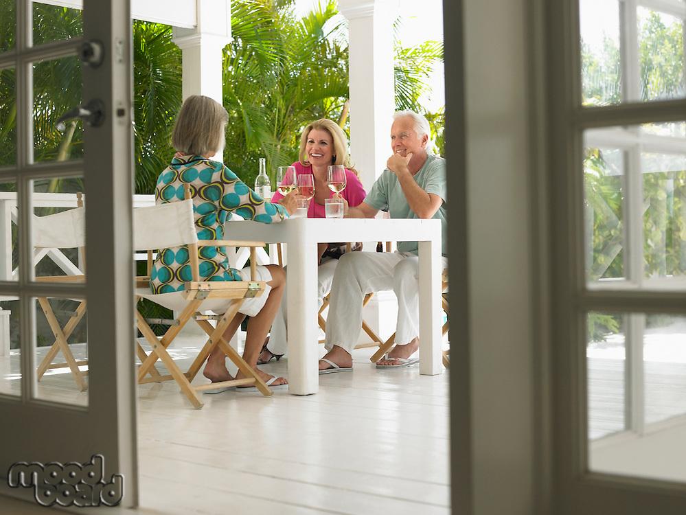 Three people sitting at verandah table