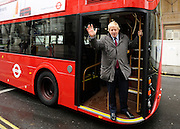 © Licensed to London News Pictures. 16/12/2011, London, UK.  BORIS JOHNSON waves from the footplate at the rear of the bus. The first bus designed specifically for London arrived in the capital today, carrying the Mayor of London BORIS JOHNSON. The bus design is based on the famous red route master buses with a rear platform for access. Photo credit : Stephen Simpson/LNP