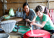 A tourist leearning how to make rice paper at a tourist stop the Mekong River in Vietnam<br /> <br />  photo by Dennis Brack