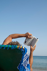 man on holiday reading a book while sitting in a lounge chair by the sea