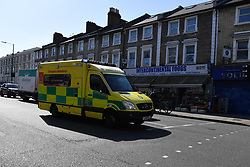 © Licensed to London News Pictures. 27/06/2019. London, UK. An ambulance in front of Intercontinental Foods supermarket in Shepherds Bush, the scene of a fatal stabbing last night. The 18 year old victim is understood to have stumbled into the shop seeking refuge after being stabbed outside by two assailants who fled down an alley. Photo credit: Guilhem Baker/LNP