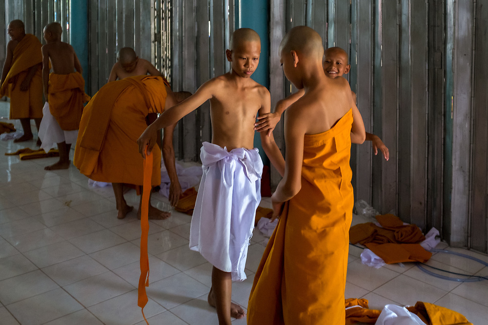 Young men put of the orange robes of a Buddhist monk in Nakhon Nayok, Thailand