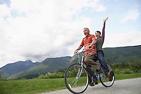 Man and woman riding on one bicycle screaming