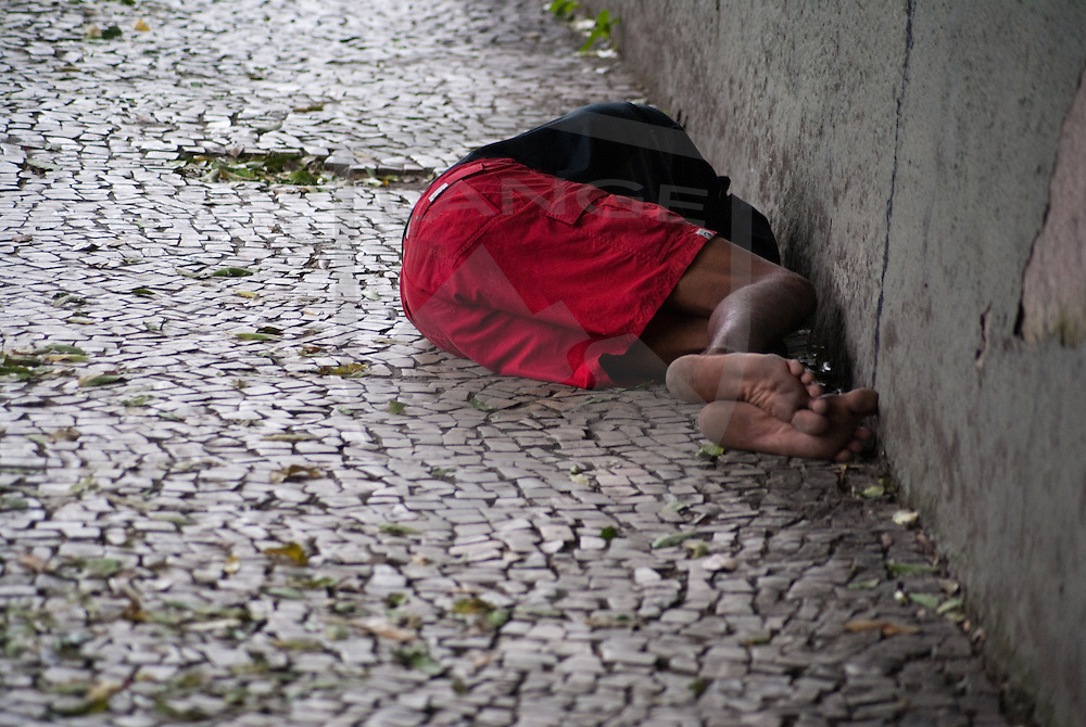 a homeless carioca sleeps on the sidewalk against a wall in centro, rio de janeiro, brazil.  the disparity in wealth distribution within the city of rio de janeiro is jarring as the government continues to implement legislation to curb the polarized socioeconomic climate.