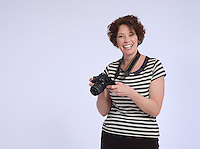 Portrait of mid adult woman holding digital camera studio shot