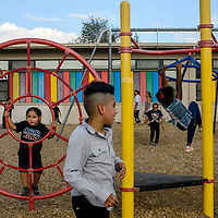 Students play on the playground equipment during a groundbreaking ceremony for a new school building at Lincoln Elementary School in Gallup Monday.