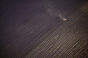 Central Valley, California near Fresno. Aerial of a tractor pulling a disc to prepare a farm field for planting.