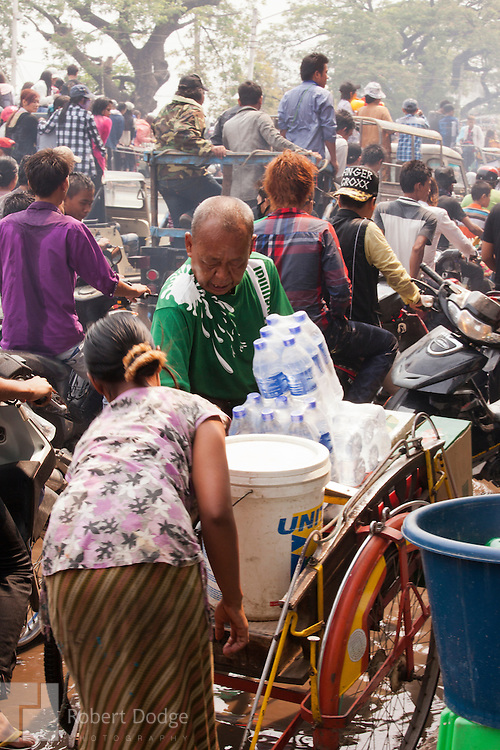 Mandalay, Myanmar- April 14, 2013: Water vendors did a brisk business during Myanmar's Thingyan Water Festival. Thingyan is held in April, one of the hottest months of the year in Myanmar. The water festival marks the country's New Year celebration and the festival includes lots of drinking, singing, dancing and theater. Wherever you are you are likely to get doused with water as the Burmese see this as a cleansing of the previous year's sins and bad luck and a blessing for good luck and prosperity in the year ahead. In the major cities of Mandalay and Yangon, large platforms are erected along major roadways and are equipped with high powered water hoses. The platforms, sponsored by large corporate donors, also have dance stages and play the latest pop and hip hop music. Thousands of residents pour into the streets by foot, motorbike and flatbed truck to get hosed under the platforms while they drink and dance. Many of the young celebrants wear their best clubbing clothes. And many of the party goers are men, having left their wives and girlfriends at home.
