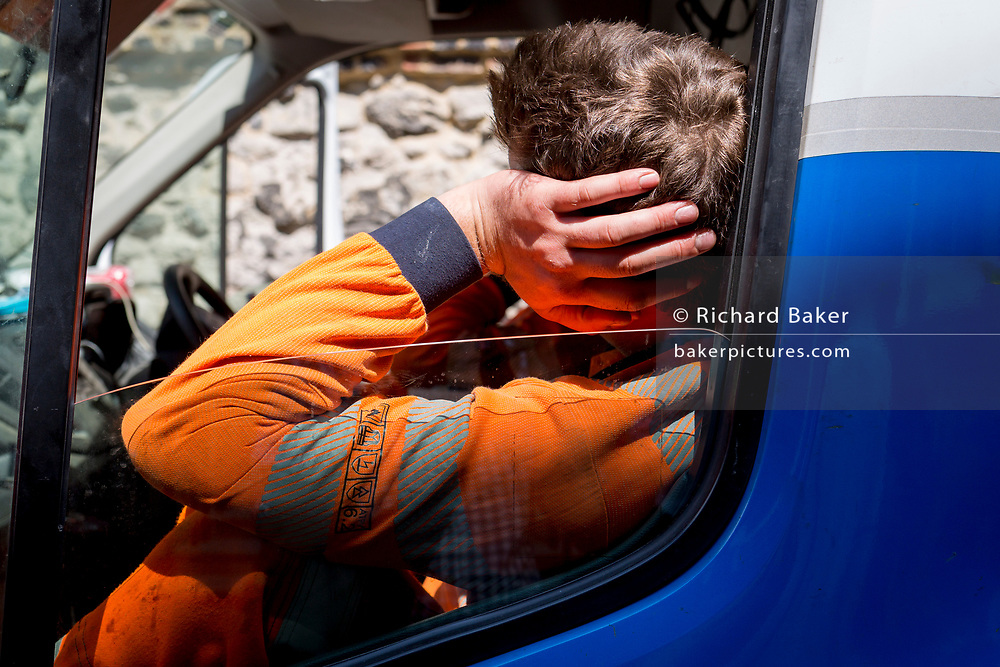 A Thames Water engineer rests in his van during repair works in Great College Street in Westminster, on 16th July 2019, in London, England.