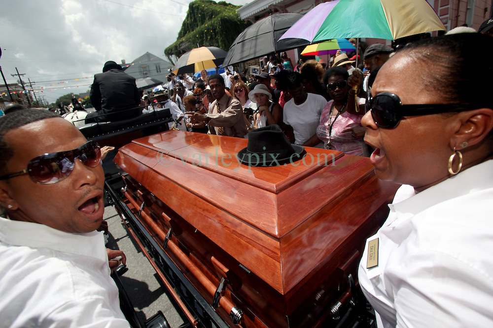 23 July 2012. New Orleans, Louisiana,  USA. .The funeral procession for 'Uncle' Lionel Batiste, drummer for the Treme Brass Band winds its way through the Treme neighbourhood..Photo; Charlie Varley.