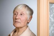 Elderly woman with short grey hair in doorway