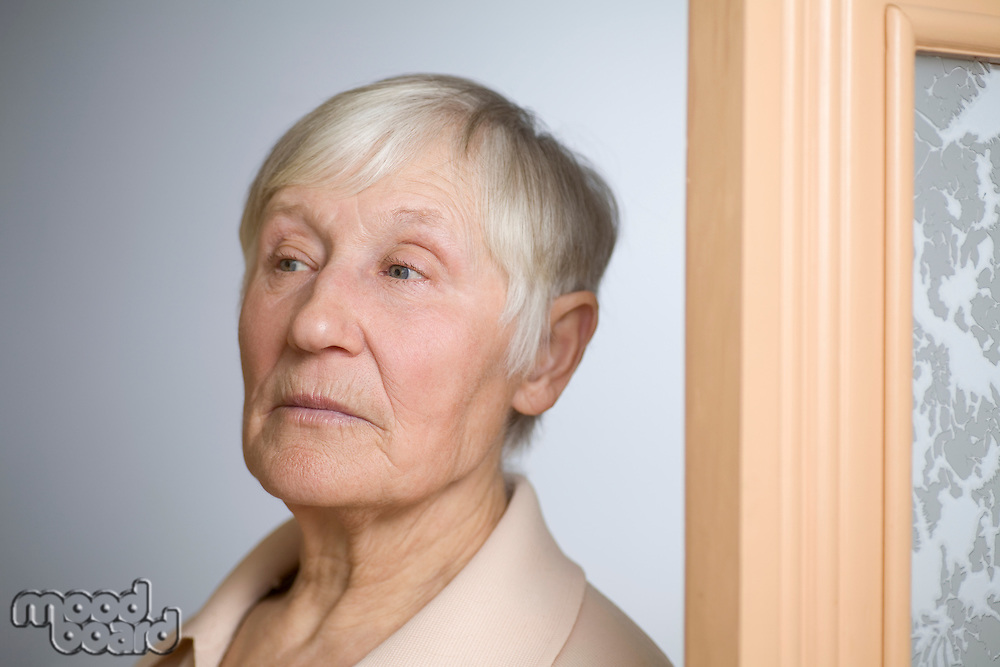 Elderly woman with short grey hair in doorway