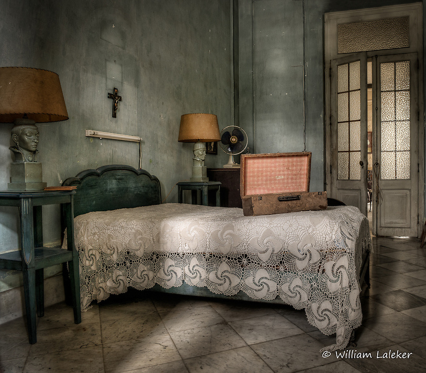 A well worn suitcase sits on a handmade bedspread. The once upscale mansion is located in the Vedado neighborhood of Havana, Cuba.