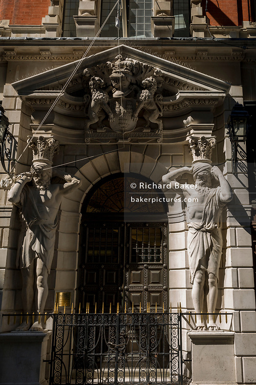 The Atlantes figure by the sculptor H.A. Pegram (1896) at the entrance of Drapers' Hall livery company in Throgmorton Street in the City of London, the capital's financial district aka the Square Mile, on 15th May 2018, in London, UK. The Drapers' Company is a Livery Company in the City of London whose roots go back to the 13th century, when as its name indicates, it was involved in the drapery trade. While it is no longer involved in the trade, the Company has evolved acquiring a new relevance. Its main role today is to be the trustee of the charitable trusts that have been left in its care over the centuries. The Company also manages a thriving hospitality business. The first Drapers' Hall was built in the 15th century in St Swithin's Lane.  It bought a Hall on the present site in Throgmorton Street in 1543 from King Henry VIII for £1,200 (about £350,000 in today's money). The Hall that the Company purchased from King Henry VIII in 1543 had been the private residence of Thomas Cromwell, Earl of Essex until his execution in 1540, when it was confiscated by the Crown.