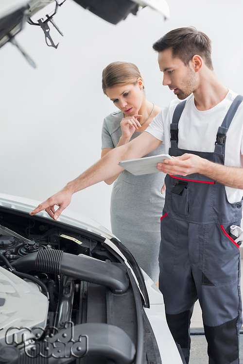 Young repair worker explaining car engine to worried customer in workshop