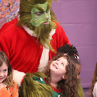 "Early Childhood Education Center student Gracie McDonald gets her photo made along with her classmates as ""The Grinch"" stops by Monday morning."