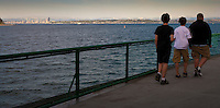 Three young men walk along the railing of a Washington State Ferry on a crossing of Puget Sound with Seattle, Washington in the background panorama