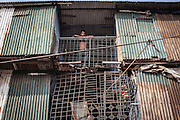 A man peeks out from the balcony of a metal structure near the bridge to Kamrangirchar in Dhaka.